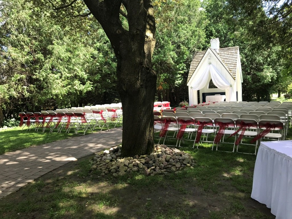 Red Organza Sashes along back row and aisle chairs