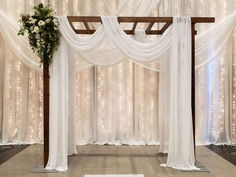 Wood Trellis Decorated for Ceremony with Waterfall of Lights Backdrop