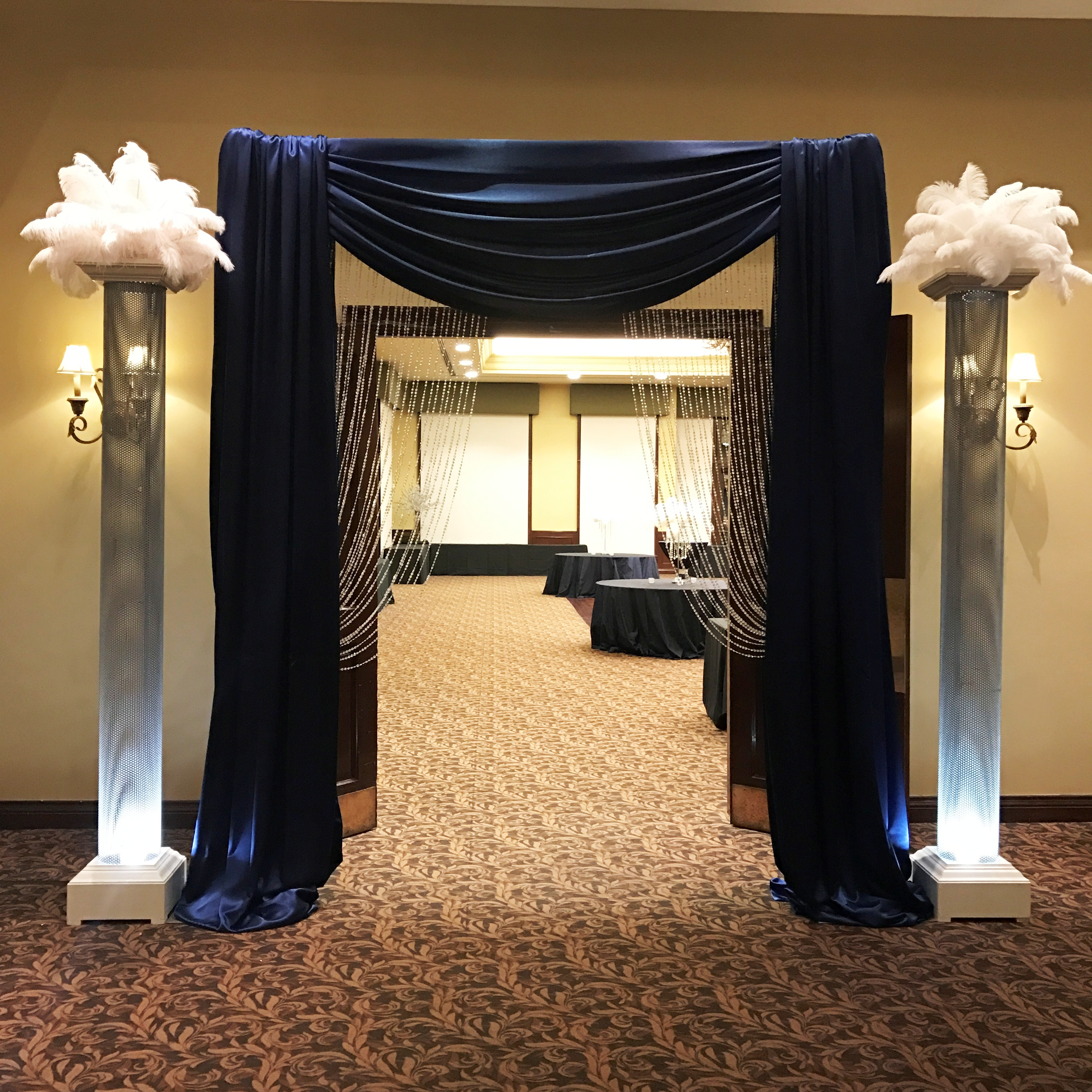 Arbour Entrance in Navy & Crystals with Uplit Silver Columns & White Feather Toppers