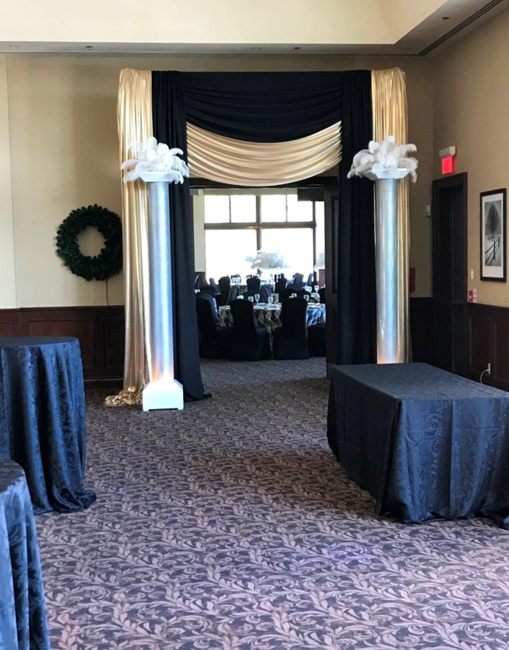 Black & Gold Entranceway with Uplit Columns & Feather Toppers